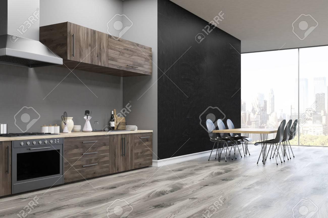 Vista laterale di un interno cucina con muro nero, bancone della cucina, un  forno e un grande tavolo. Rendering 3D.