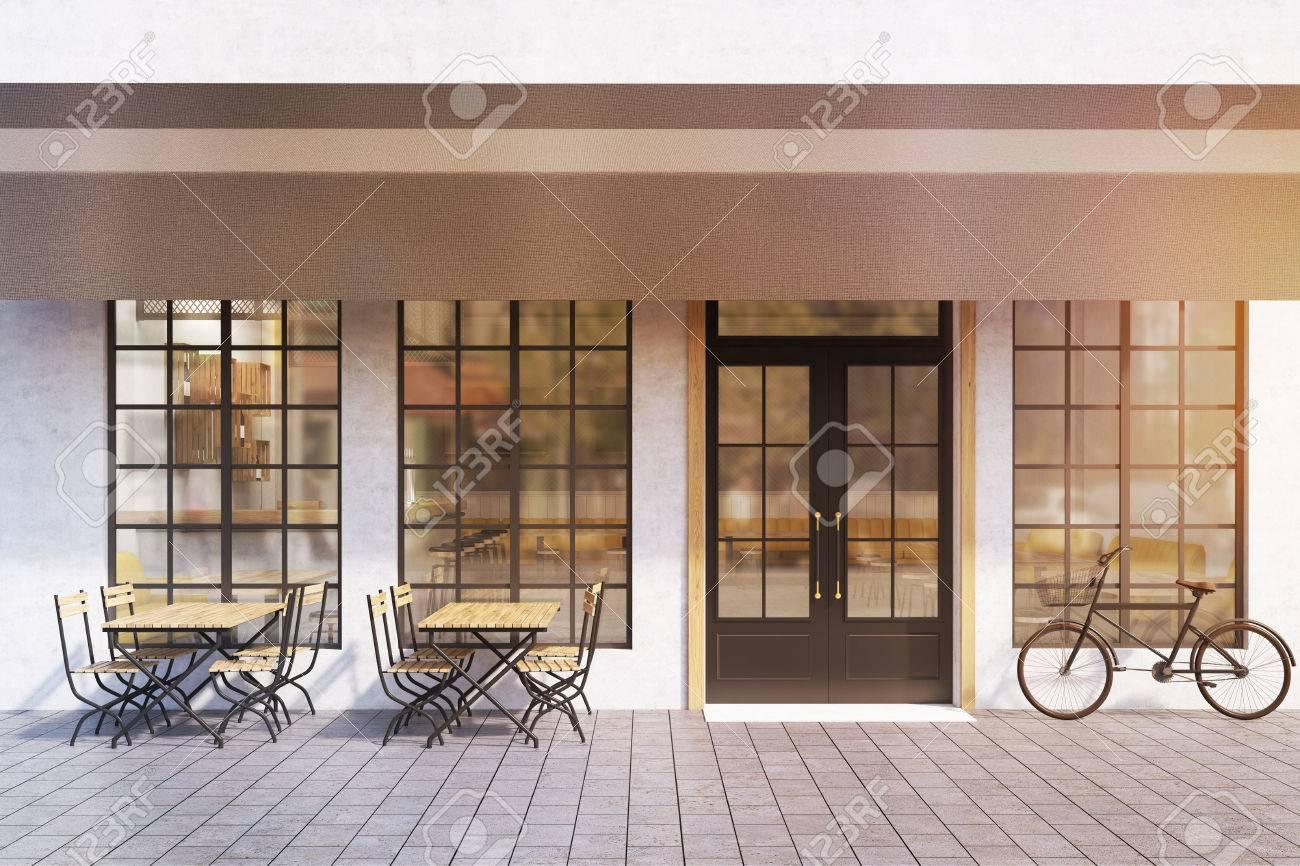 L\'ingresso a un caffè con ampie finestre, tavoli in legno con sedie e una  bicicletta vicino all\'ingresso. rendering 3d. Modello. Viraggio