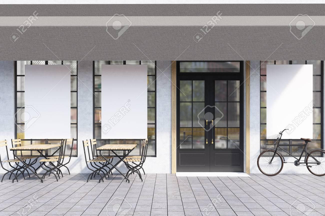 Esterno del caffè con grandi finestre con poster, tavoli in legno con sedie  e una bicicletta vicino all\'ingresso. Rendering 3D. Modello.