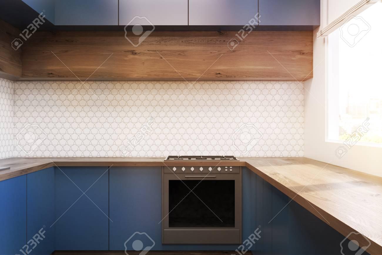 Interior de la cocina moderna con muebles azules, mesa de madera y un  horno. Concepto de un piso cómodo. Representación 3d Imagen entonada