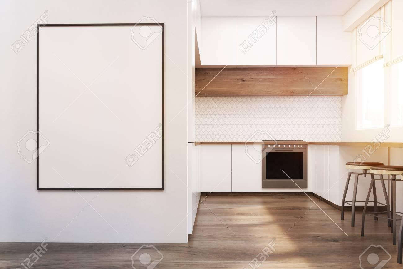 Interno cucina moderna con mobili bianchi, tavolo in legno e un forno. Un  poster incorniciato è appeso a un muro. Concetto di un appartamento ...