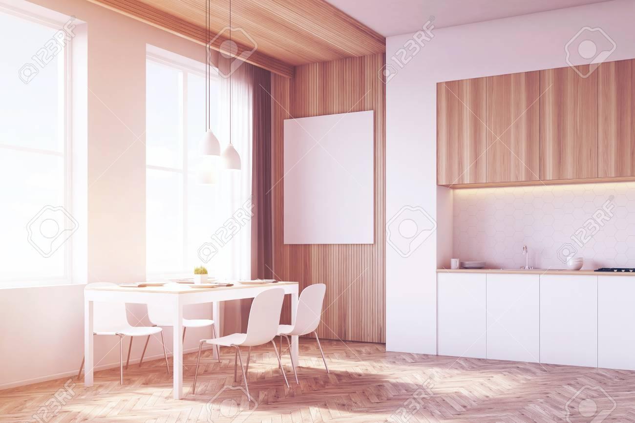 Vista laterale dell\'interno della cucina con tavolo e tavolo da pranzo  circondato da sedie. C\'è un grande poster verticale su una parte in legno  ...