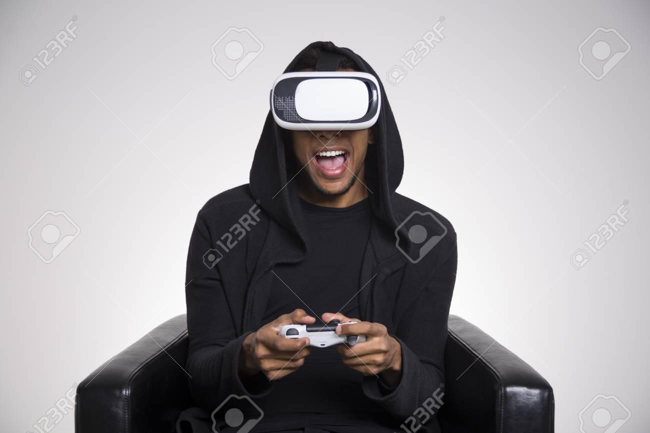 4d070c9012b1 Chico afroamericano en una sudadera con capucha negro está jugando un juego  de realidad virtual. Él es la celebración de un controlador y sentado ...