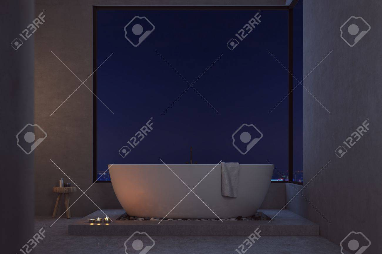 Dark Bathroom Lighted With Candles. Large Bathtub With A Towel ...