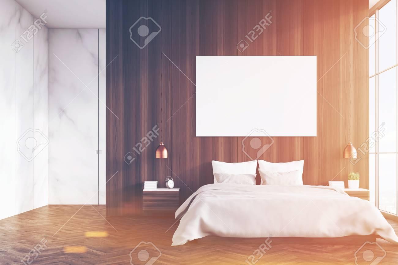Vue frontale d\'un intérieur de chambre à coucher avec un lit king size, des  murs en bois et en marbre sombre, une fenêtre panoramique et une ...