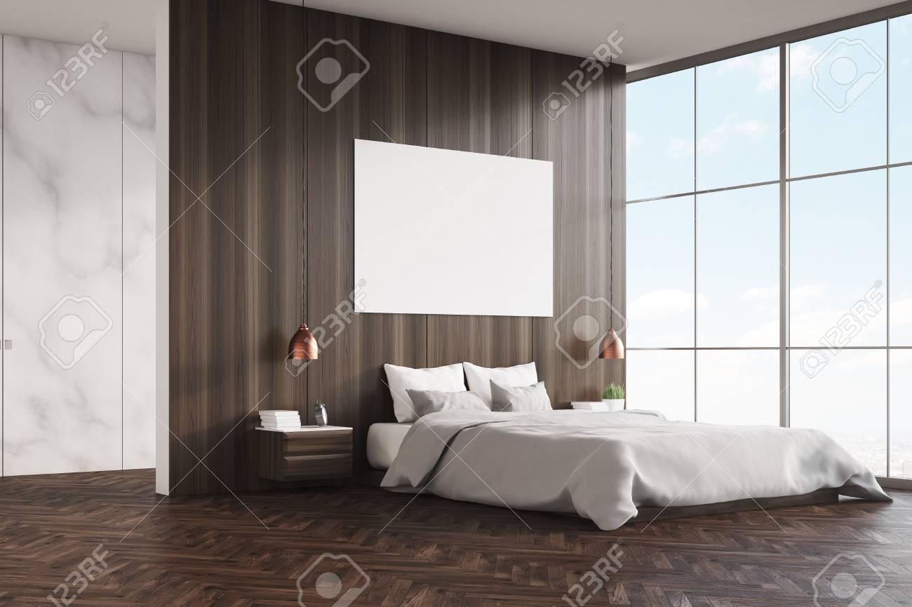 Vue latérale d\'une chambre à coucher avec un lit king size, des murs en  bois et en marbre, une fenêtre panoramique et une affiche horizontale. ...