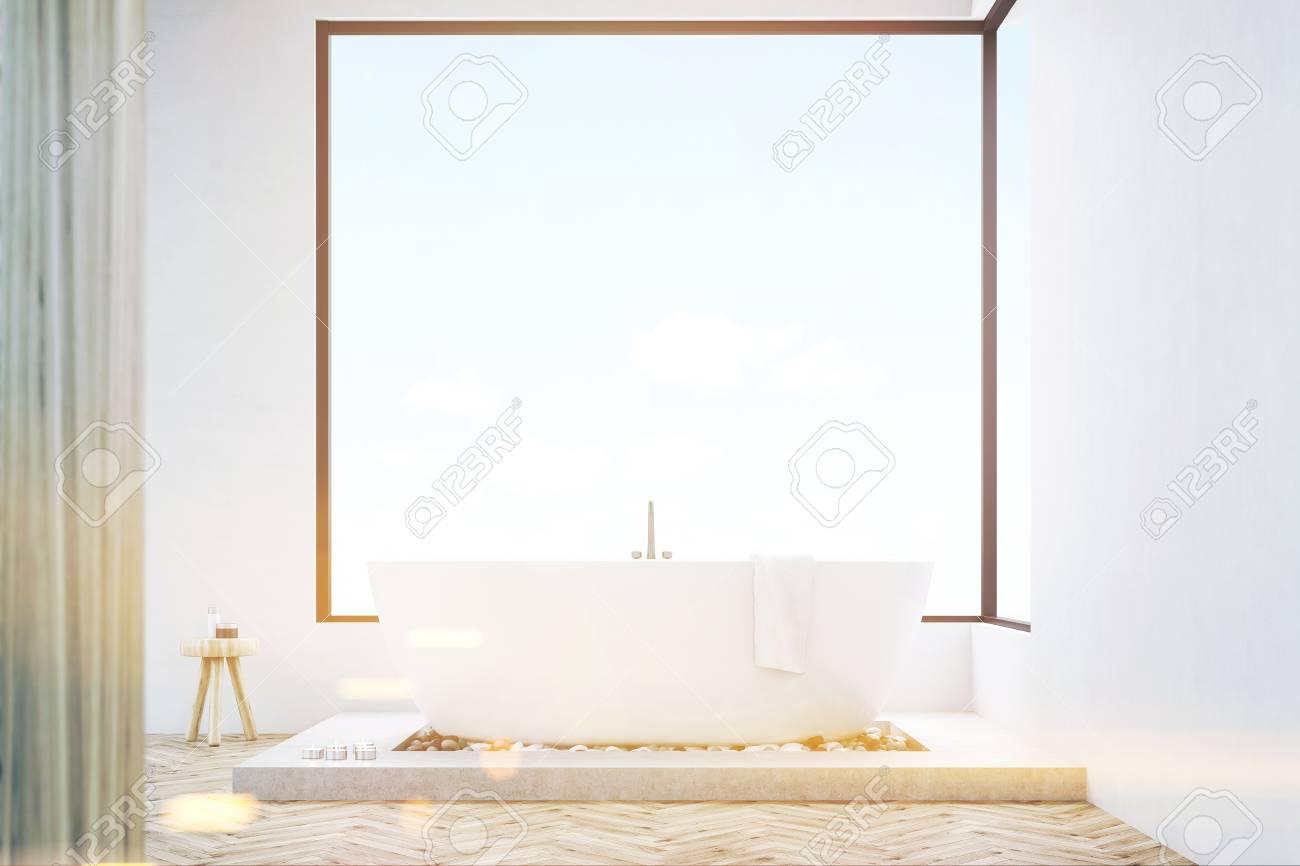 Frontansicht Eines Badezimmer Interieur Mit Einer Holzwand, Weiße Badewanne  Mit Einem Handtuch Und Panoramafenster