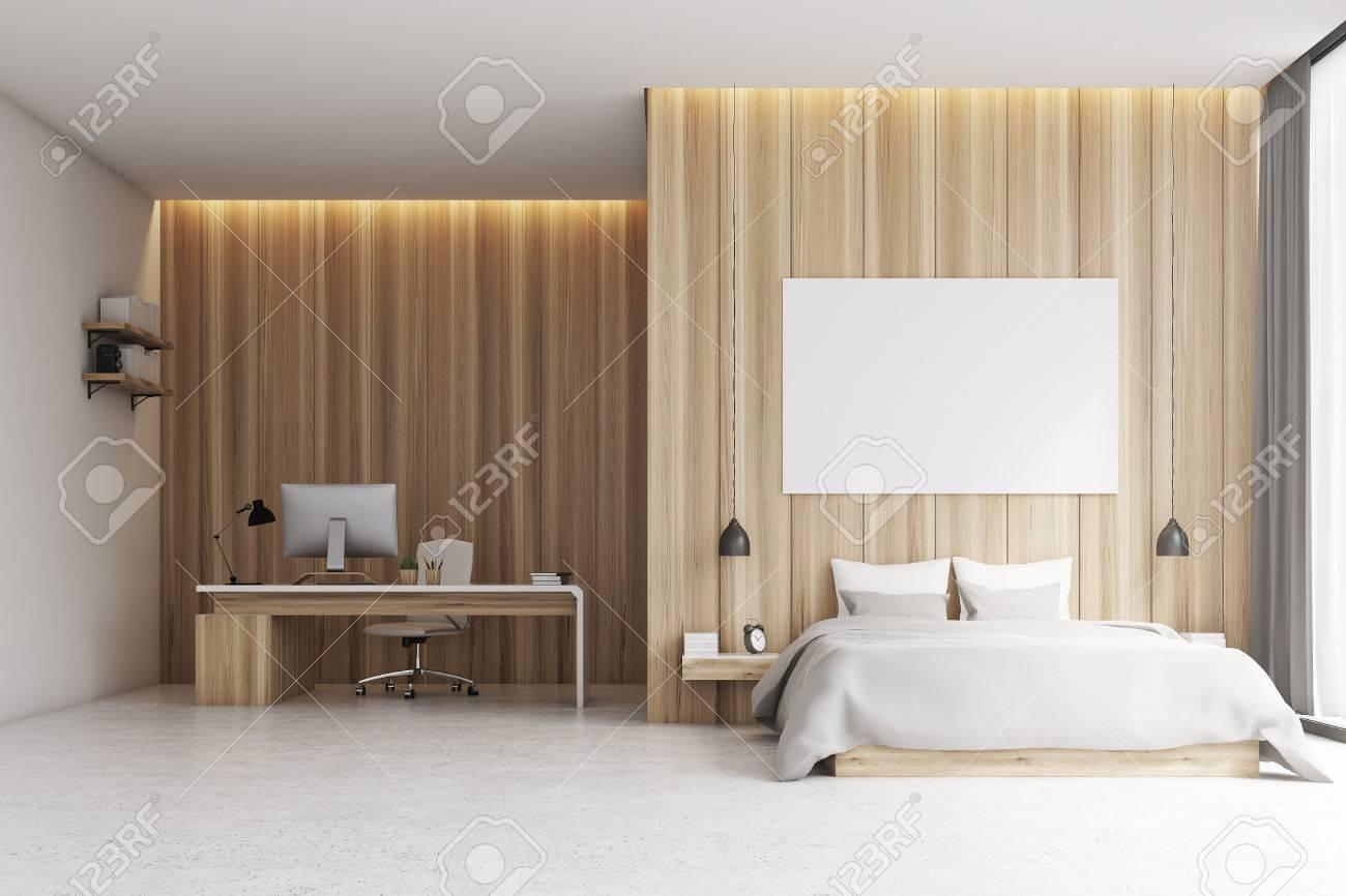 Interni Camera da letto con un angolo studio. C\'è un grande letto  matrimoniale con un poster sopra di esso e una scrivania con un computer e  una sedia ...