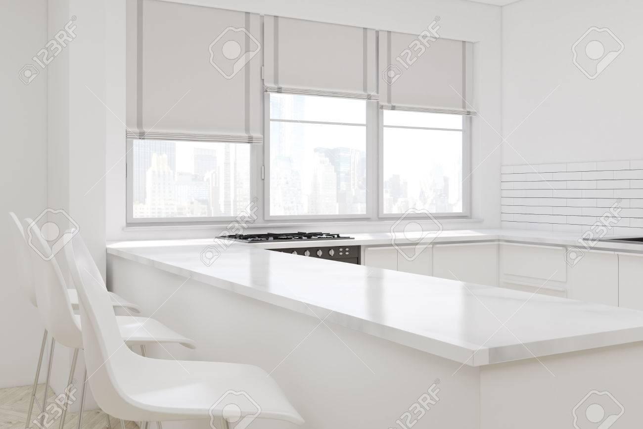 Hoek van een witte keuken met een gangpad drie stoelen een oven