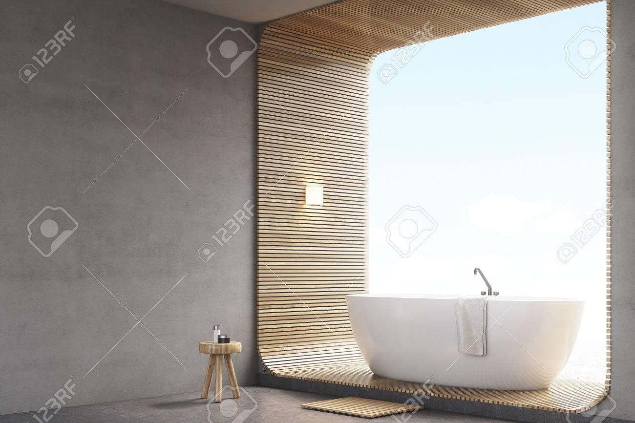Coin de salle de bain avec des murs en béton gris et une baignoire debout  sur un élément de décoration en bois. Rendu 3D. Maquette.