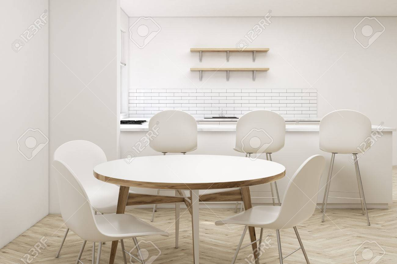 Close Up Of A Round Table In A White Kitchen With An Aisle Three