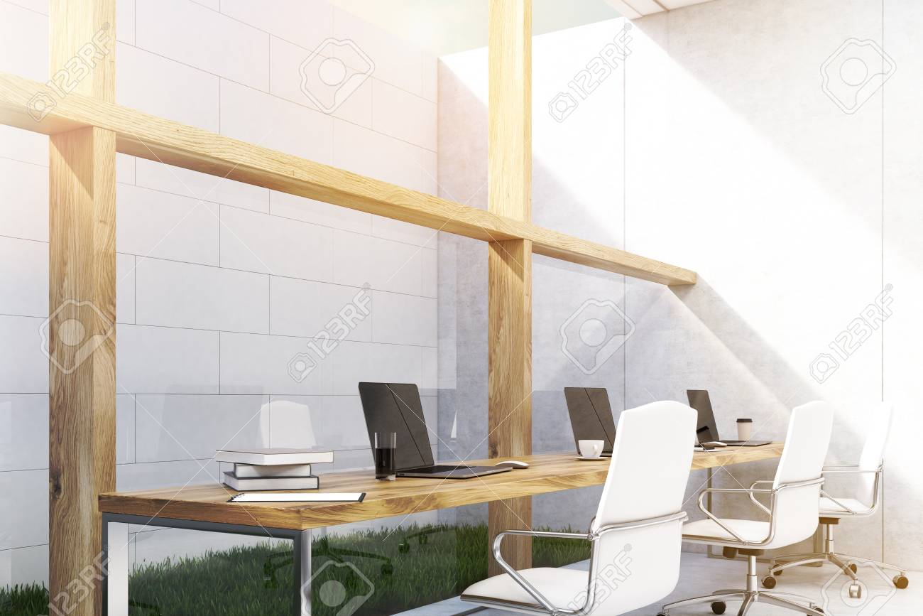 Long office table is standing near a white brick wall on a patch of grass