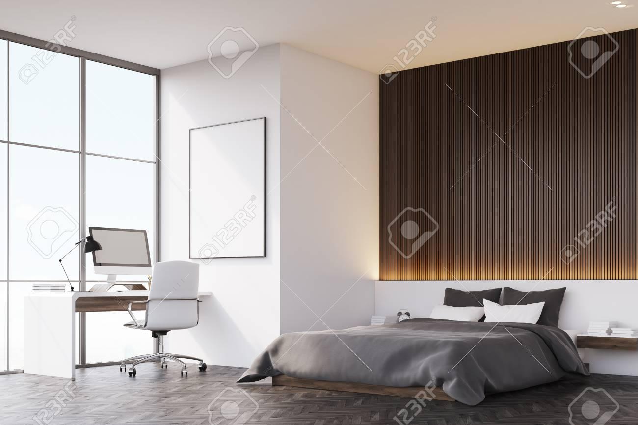 Vista laterale della camera da letto con una parete di legno. C\'è un  comodino e un poster verticale incorniciato su una parete. Una tabella è in  piedi ...