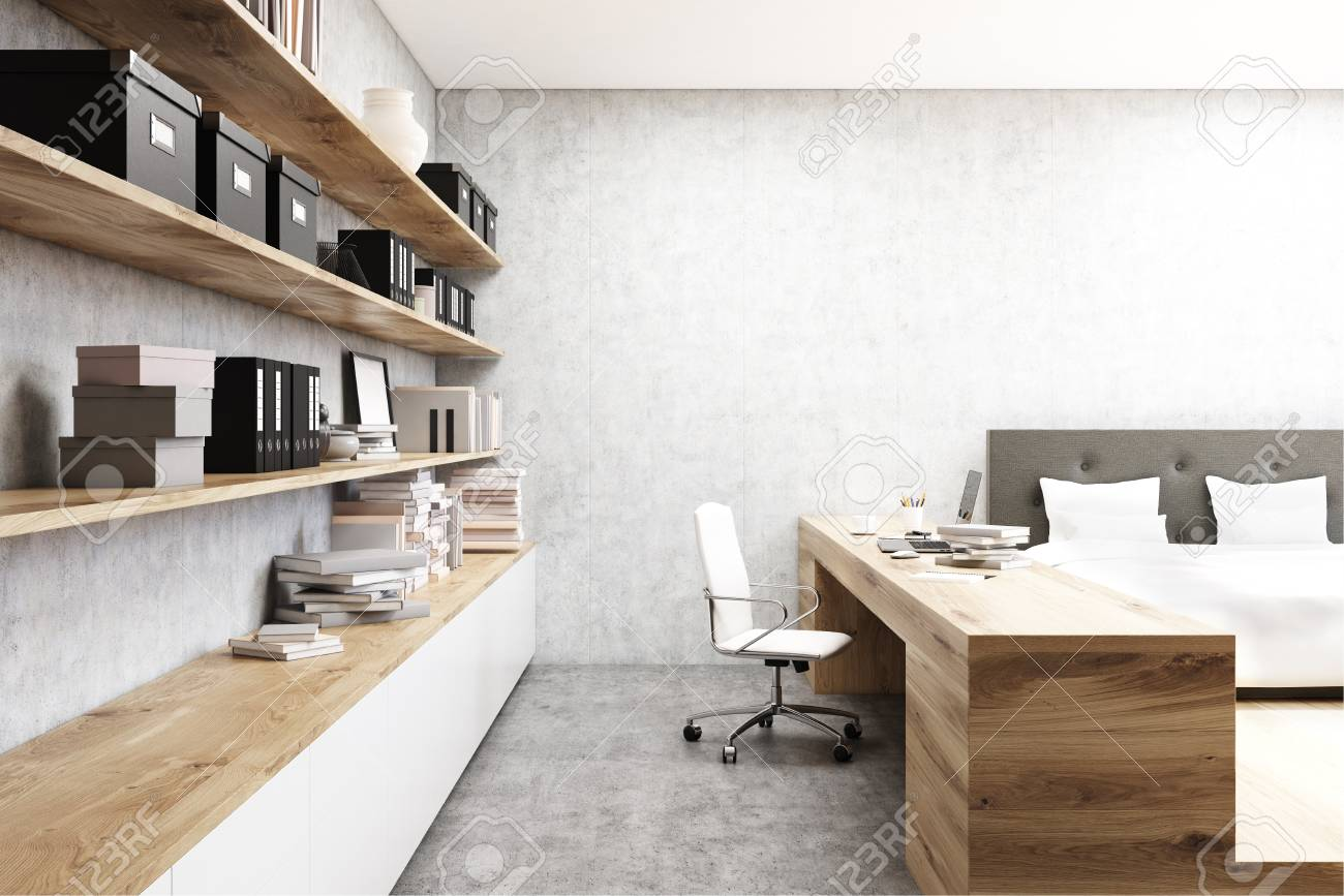 Primo piano di un tavolo in un ufficio a casa in una camera da letto. C\'è  un letto con un tavolo a fianco di esso e mensole sulla parete di cemento.  ...