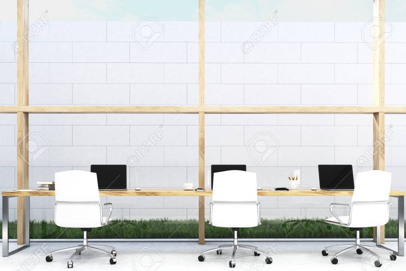 Front View Of Long Office Table Standing Near A White Brick Wall