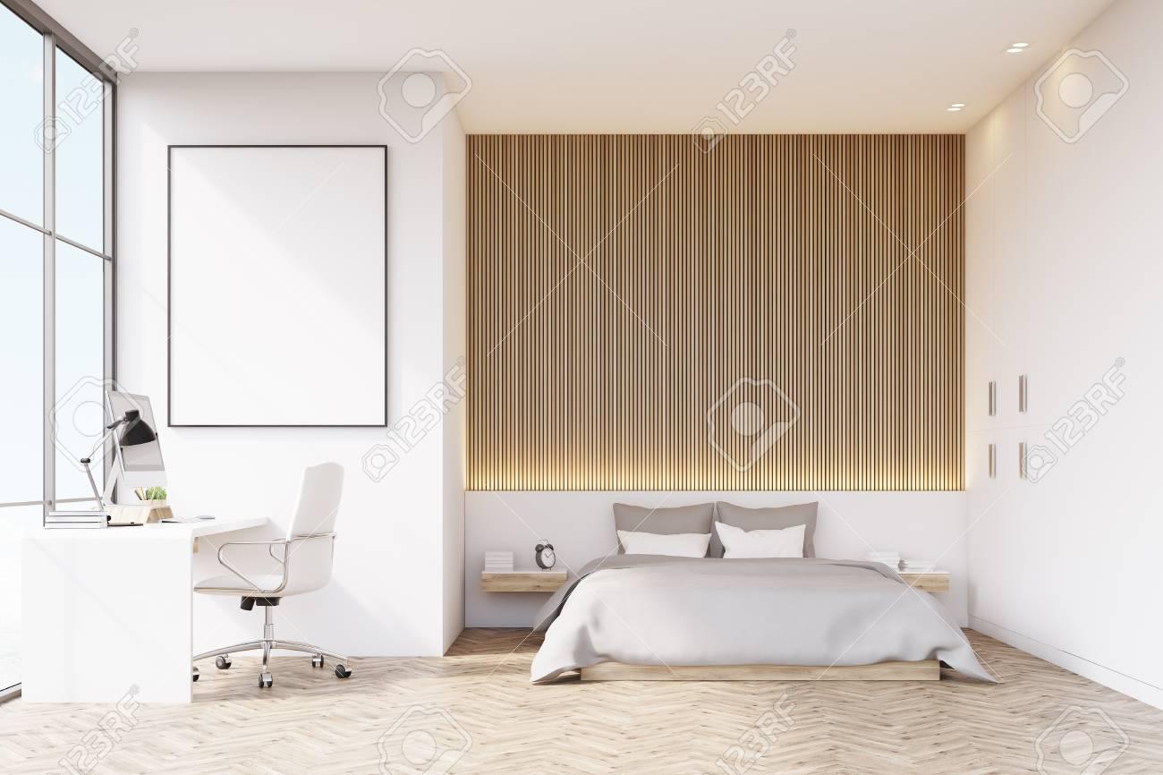 Camera da letto con una parete di legno e pavimento. C\'è un comodino e un  poster verticale incorniciato su un muro. Un tavolo è nella parte sinistra  ...