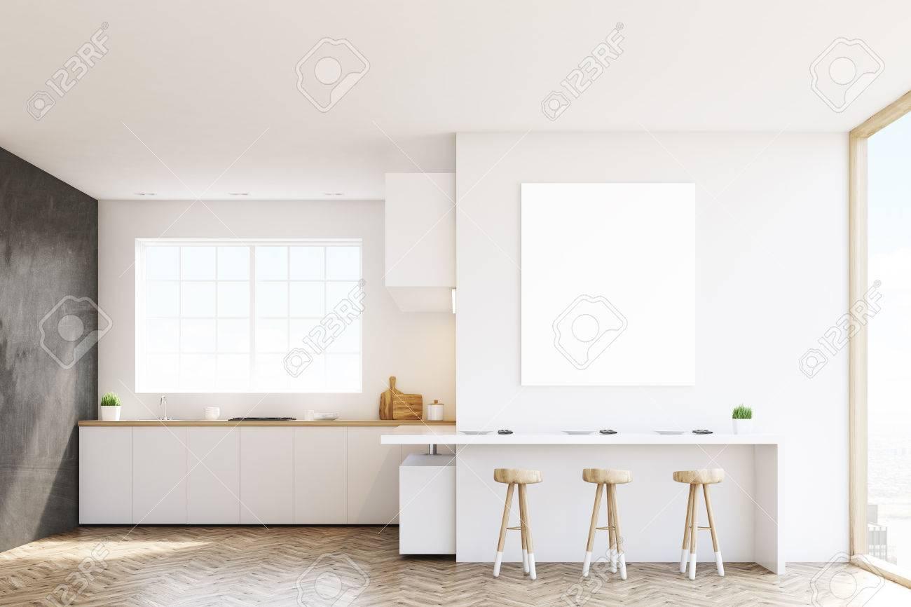 cocina con una ventana encimeras una mesa y tres taburetes paredes blancas y