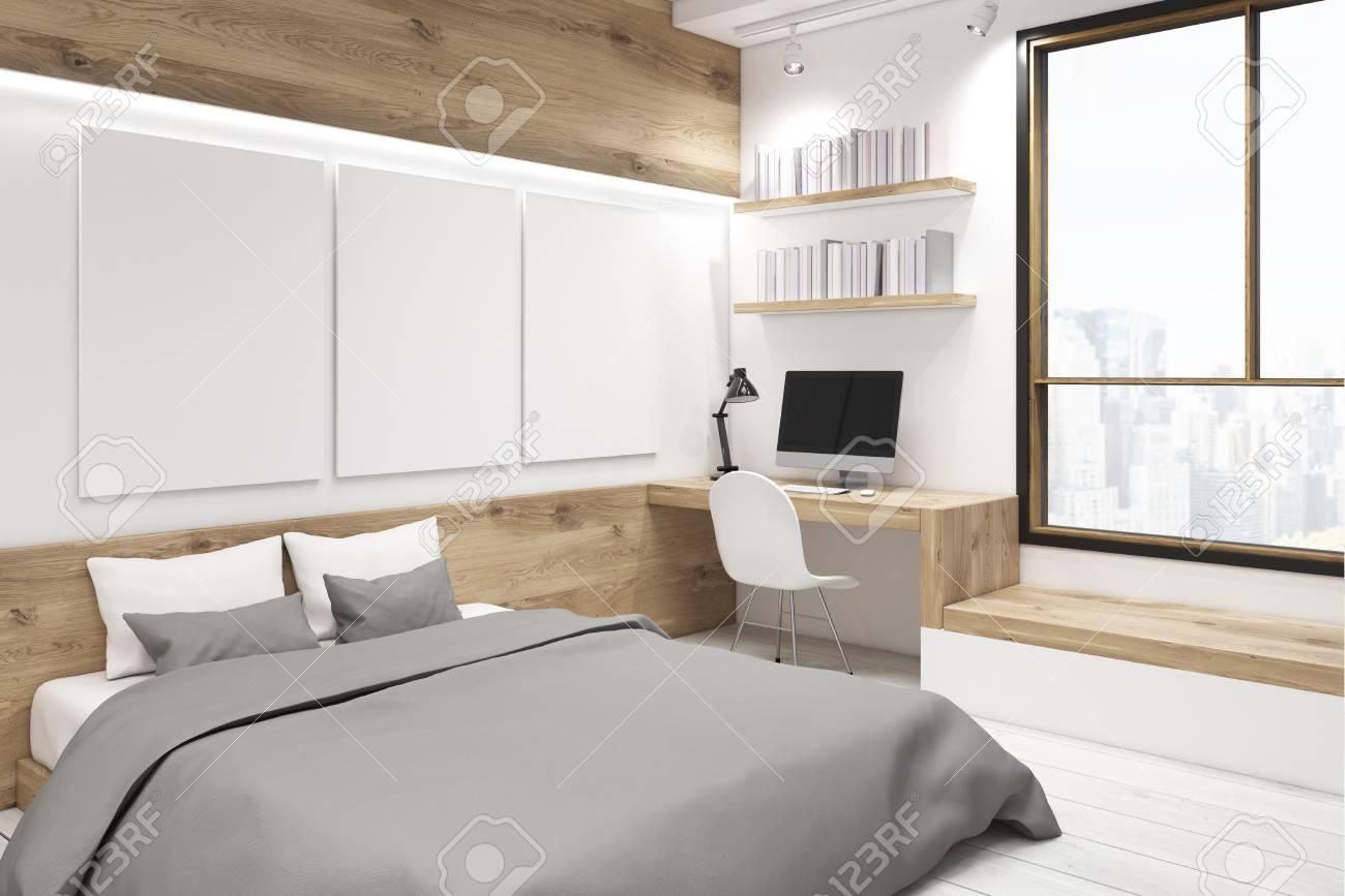Angolo della camera da letto interno con una galleria di foto. C\'è un  tavolo di legno, due librerie e tre grandi poster verticali appesi al muro.  ...