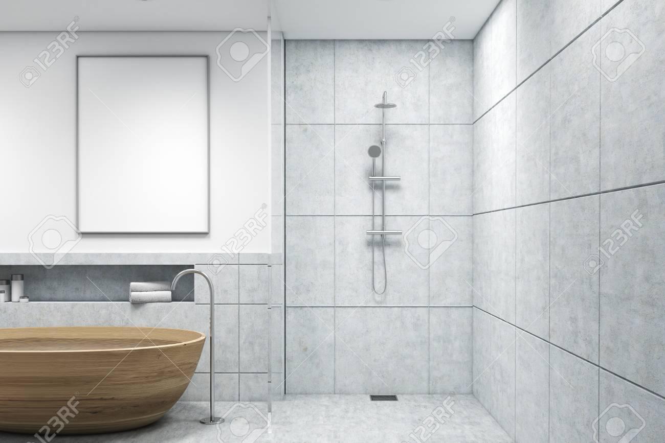 Cuarto de baño con bañera de madera, una ducha, paredes blancas y pequeñas  lámparas de techo redondas. Hay un póster vertical enmarcado en la pared.  ...