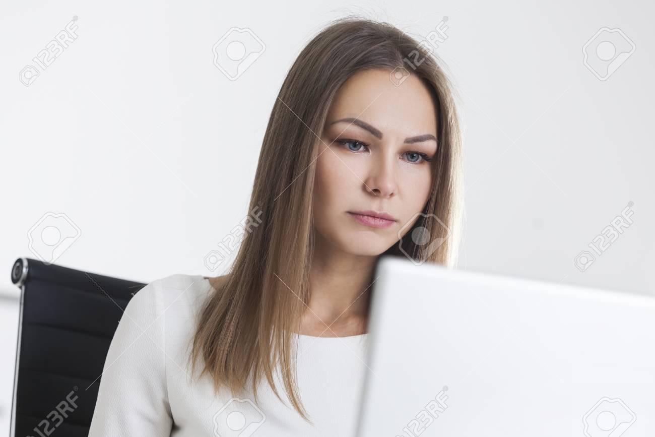 950a67d2e0 Foto de archivo - La empresaria rubia seria se está sentando en un sillón  negro y está mirando su computadora portátil en el escritorio.