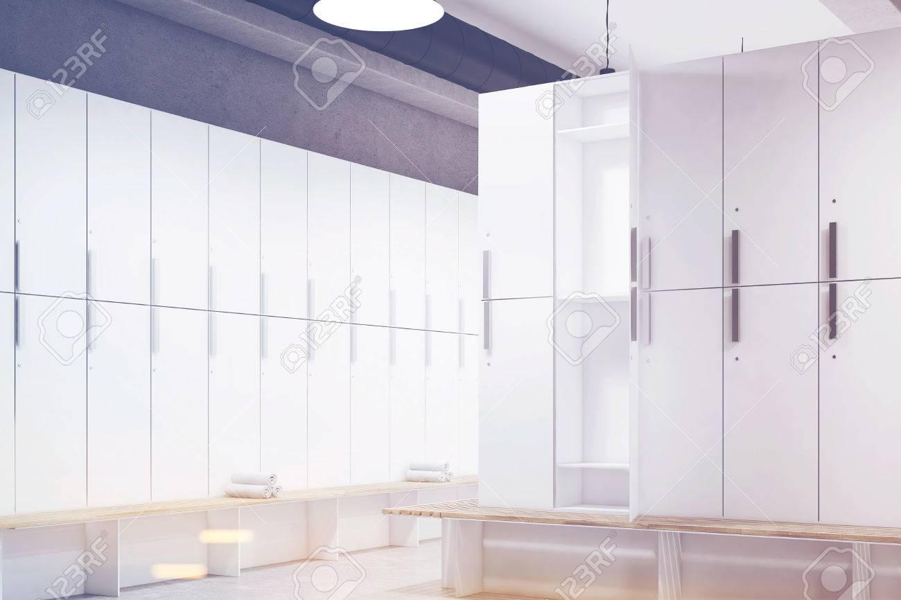 Coin d\'un vestiaire avec des murs gris, une rangée de casiers de rangement  en bois près du mur et un banc avec des serviettes enroulées. Rendu 3D. ...