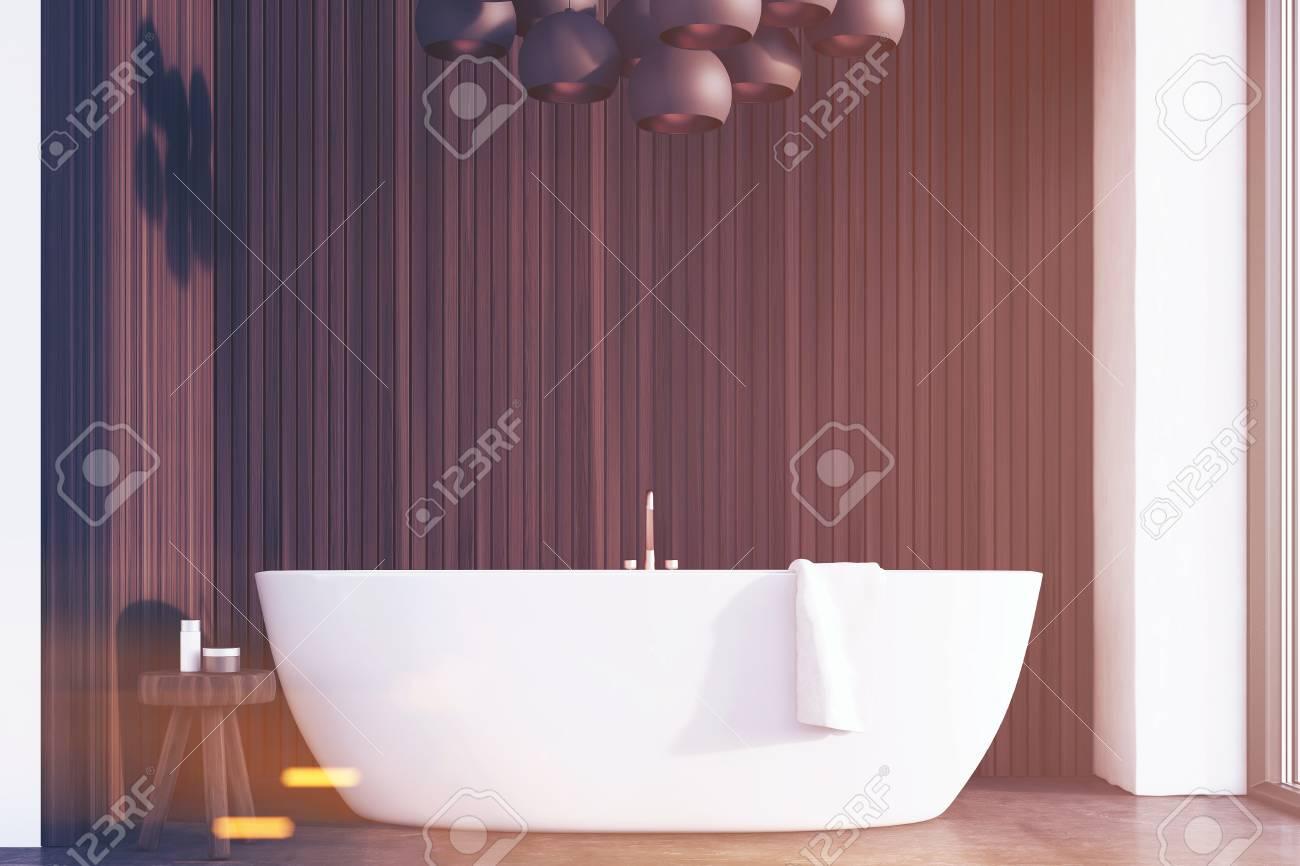 Interno del bagno con vasca bianca una sedia con prodotti per il