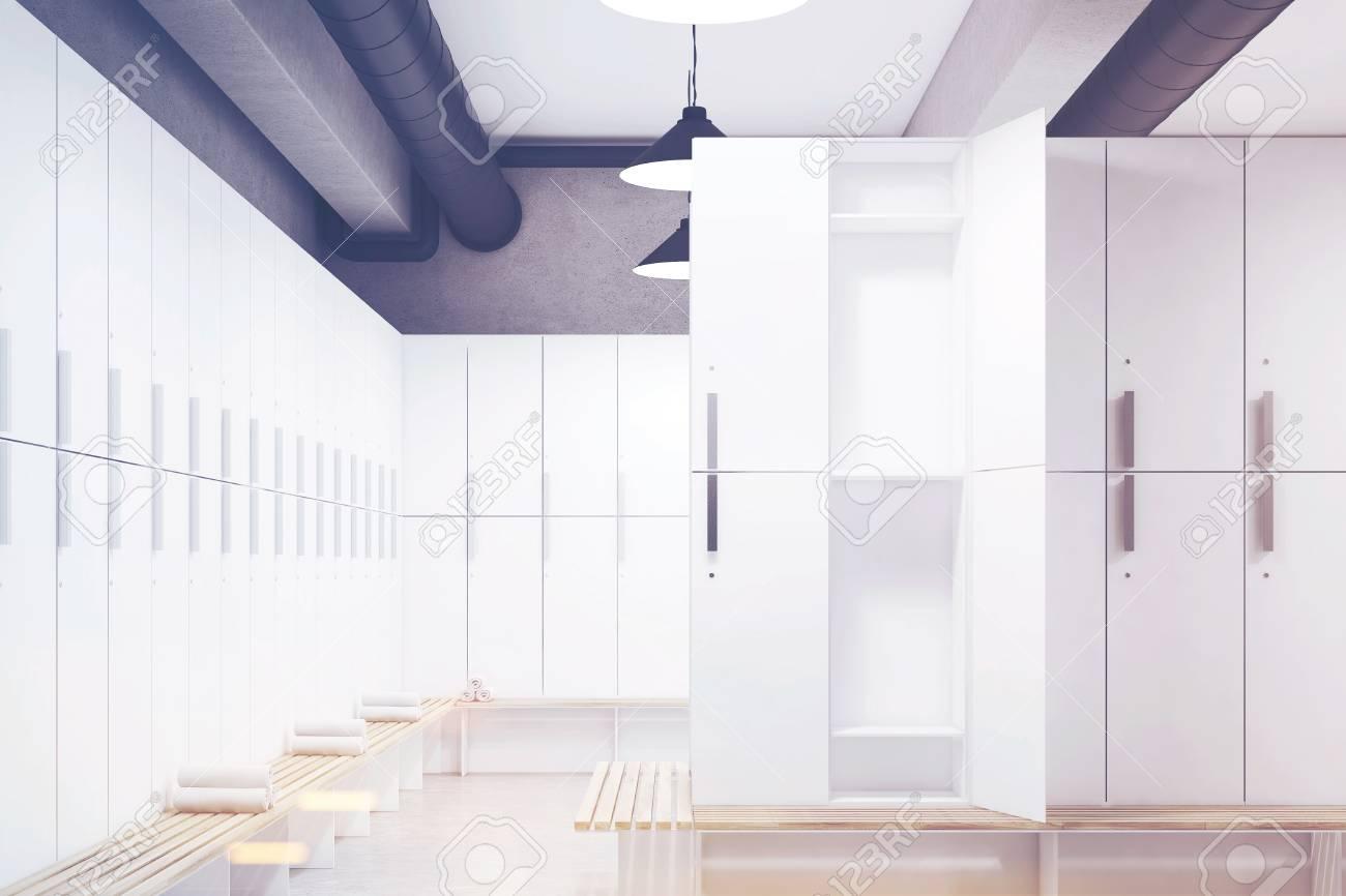 Vestiaire avec des murs gris, une rangée de casiers de rangement en bois  près du mur et un banc avec des serviettes roulées dessus. Rendu 3D  Maquette. ...