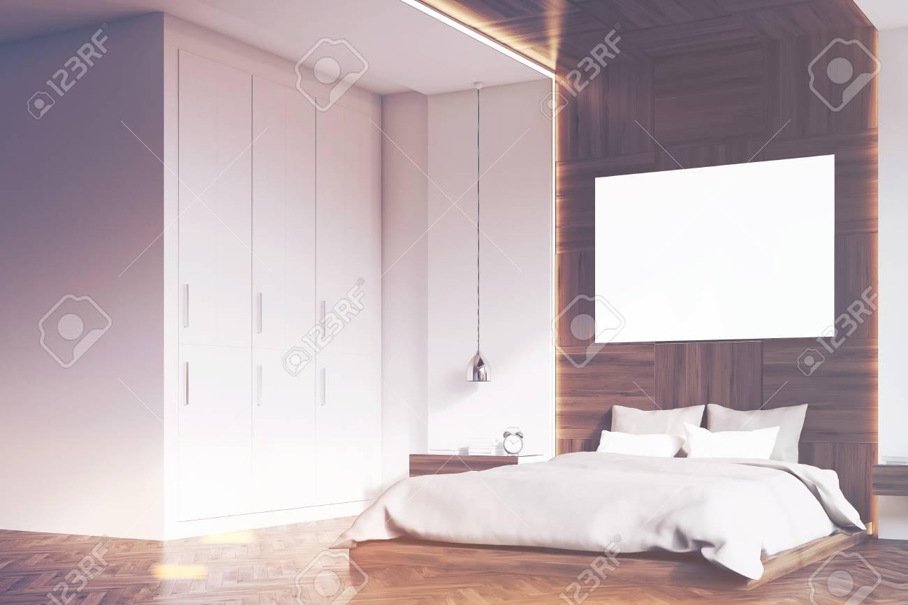 Videata laterale di un interno camera da letto con pareti in legno e un  poster su di loro. C\'è un grande letto, lampade e due comodini. Rendering  3D. ...