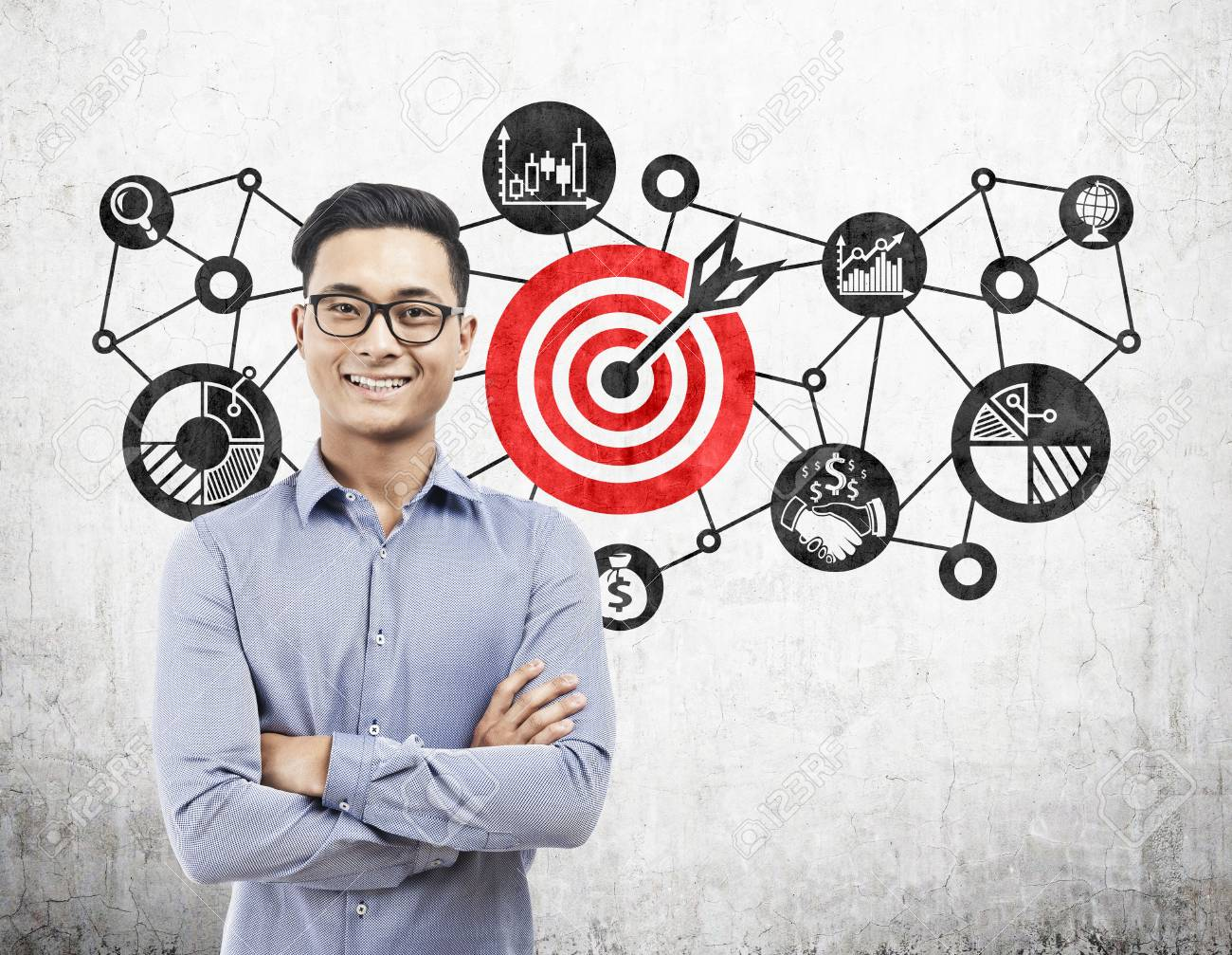 Portrait of an Asian businessman wearing glasses and standing with crossed arms near a target sketch on concrete. - 87538131