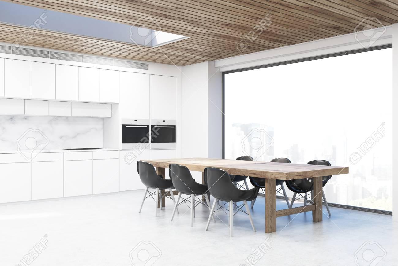 Angolo di una cucina con un lungo tavolo e sei sedie nere. C\'è un contatore  bianco sullo sfondo. Rendering 3D
