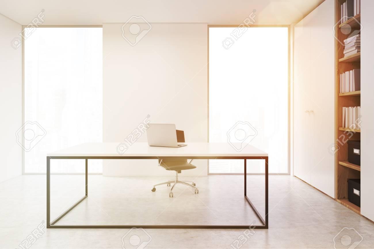 Libreria Ufficio Bianco : Ceo minimalista ufficio con un computer portatile in piedi su un