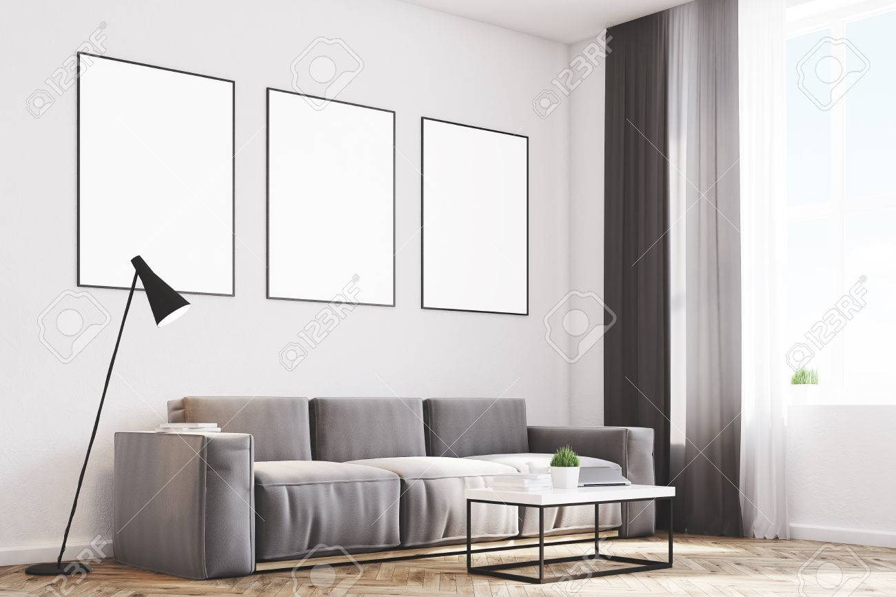 Side View Of A Living Room With Gray Walls, A Long Sofa And Three ...