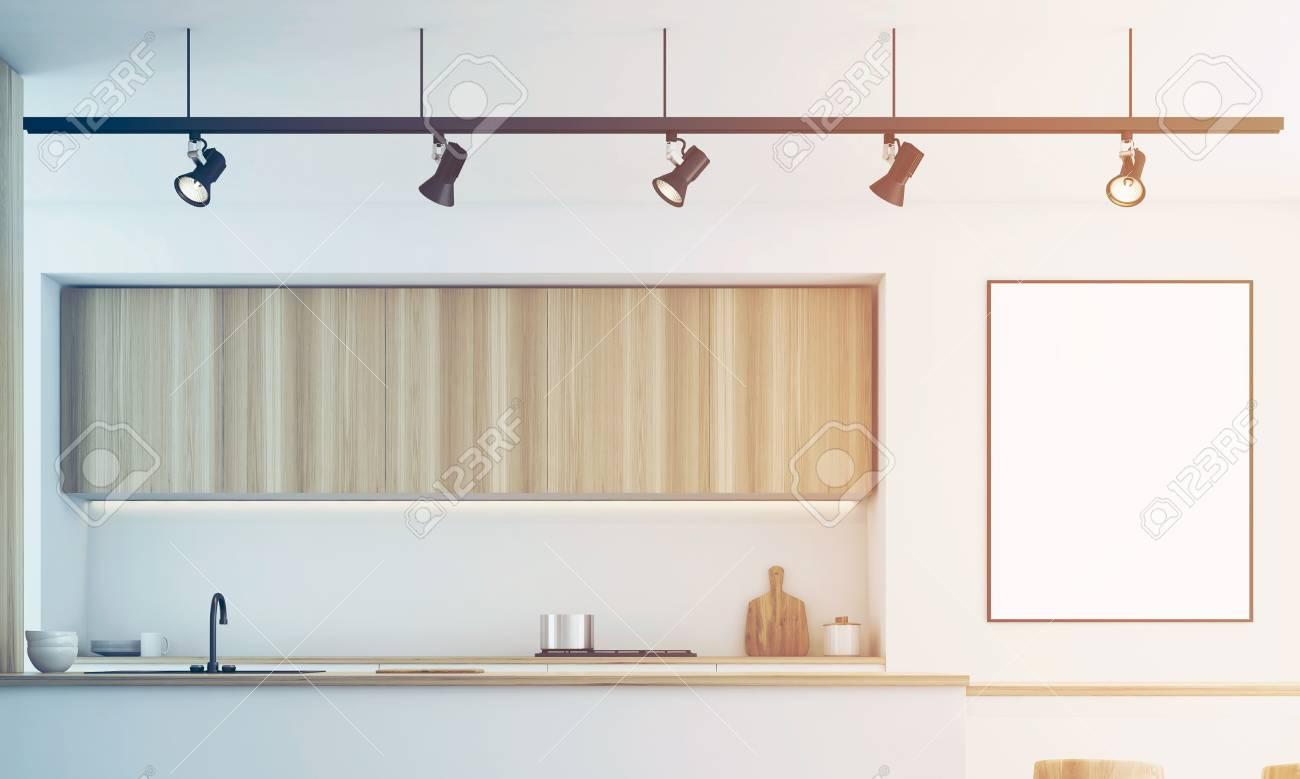 Primo piano di una cucina bianca con un bar e mobili in legno chiaro. C\'è  un poster incorniciato vuoto su un muro. Rendering 3D, mock up, immagine ...