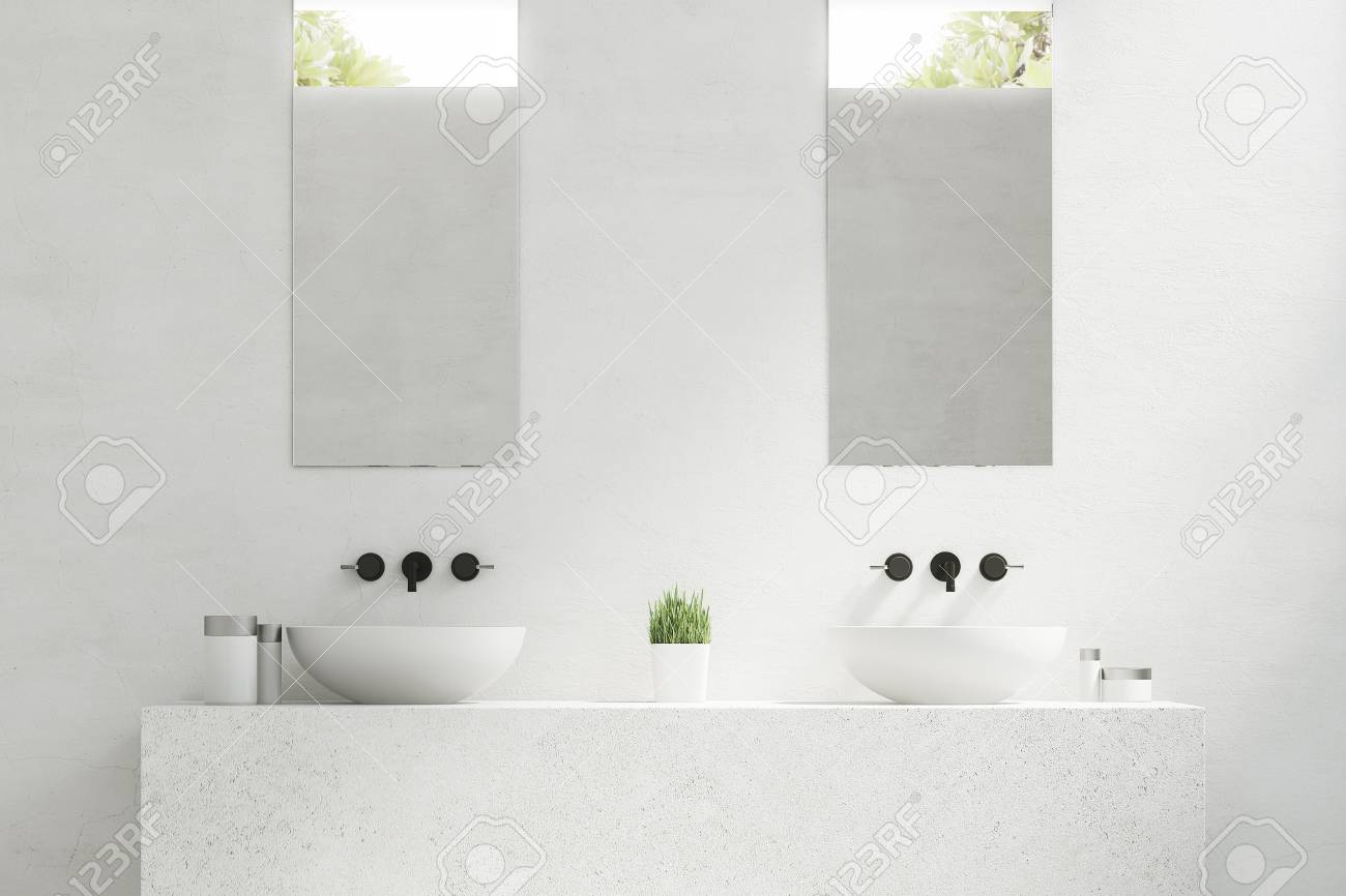Close Up Of Two Bathroom Sinks With Mirrors Hanging Above Them ...