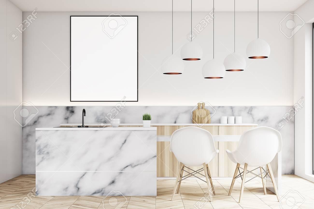 Interior de la cocina moderna con una pequeña mesa, dos sillas blancas,  encimeras de mármol y un cartel vertical enmarcado en una pared. ...
