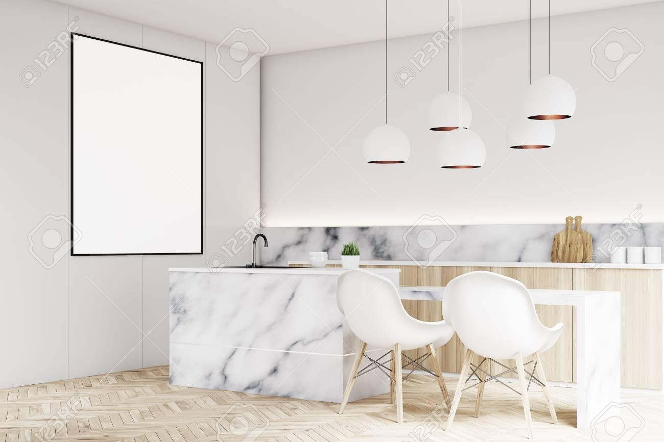 Esquina de un interior de cocina moderna con una pequeña mesa, dos sillas  blancas, encimeras de mármol y un cartel vertical enmarcado en una pared.  ...