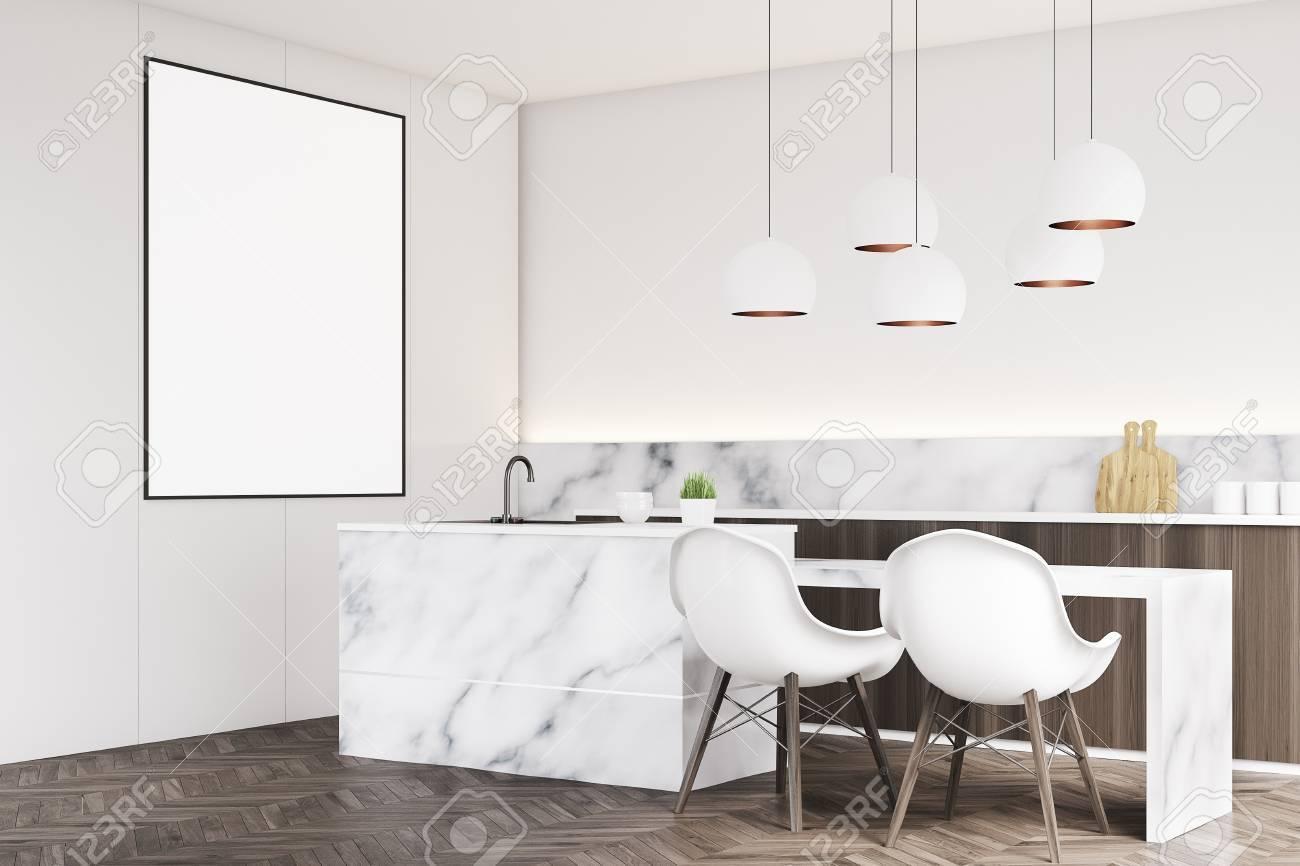 Esquina de un interior de cocina de mármol con una mesa pequeña, dos sillas  blancas, mostradores y un cartel vertical enmarcado en una pared. ...