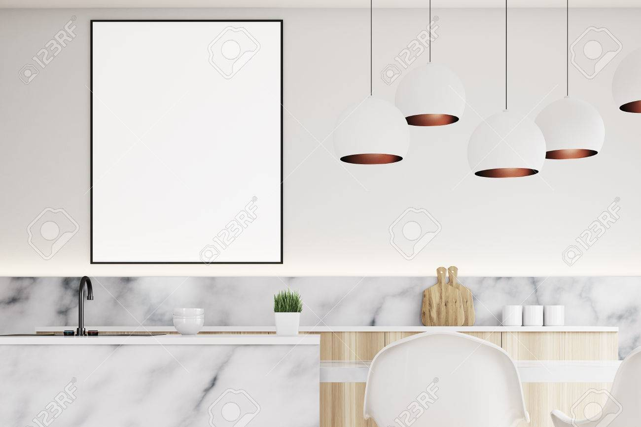 Cerca de un interior de cocina moderna con una mesa pequeña, dos sillas  blancas, encimeras de mármol y un póster vertical enmarcado en una pared.  ...