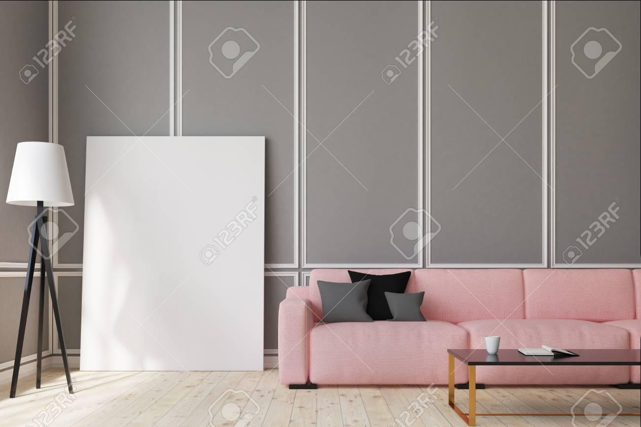 Salon avec des murs gris, un long canapé rose avec des coussins gris et  noirs et une table basse rectangulaire avec un livre ouvert dessus. Affiche  ...