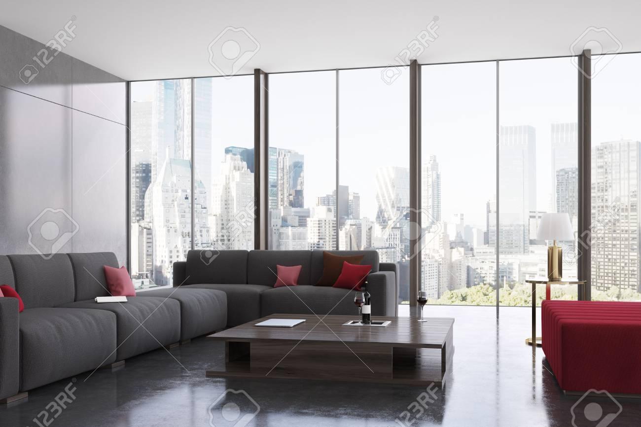 Intérieur de salon rouge et gris avec deux canapés noirs avec des coussins  debout à côté d\'une table basse carrée avec une bouteille de vin. Fenêtres  ...