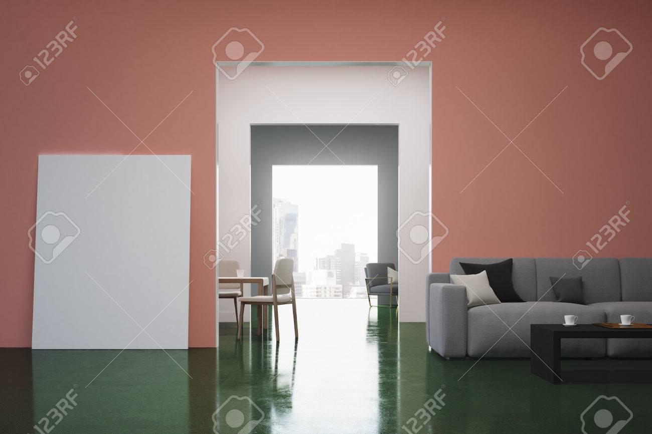 Intérieur de salon rose et vert avec un canapé gris, des coussins colorés  et une affiche verticale debout près d\'une porte. Rendu 3D, maquette