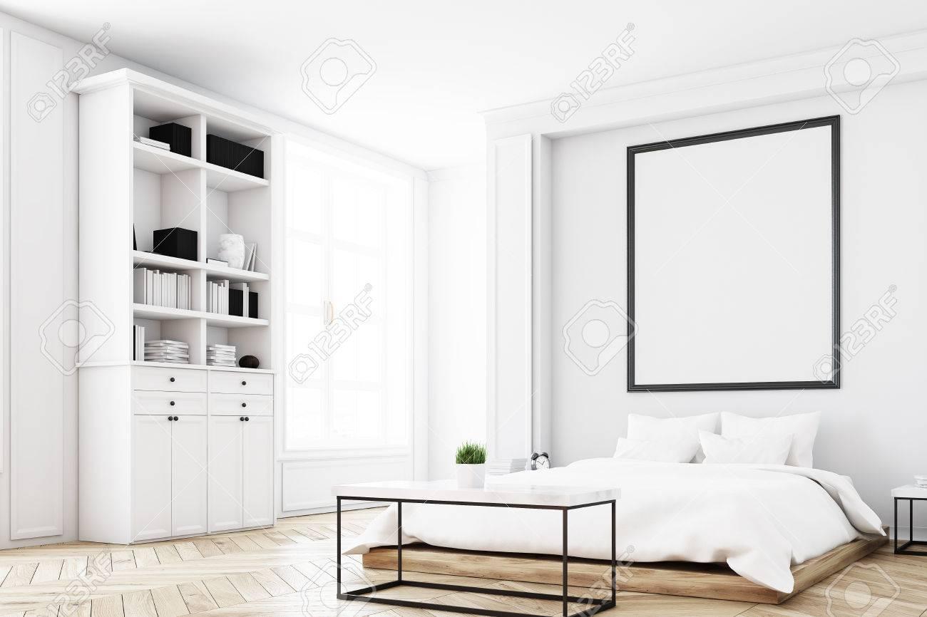 Angolo di un interno bianco della camera da letto con un letto  matrimoniale, un tavolino da caffè, una libreria vicino a un muro e  un\'immagine ...