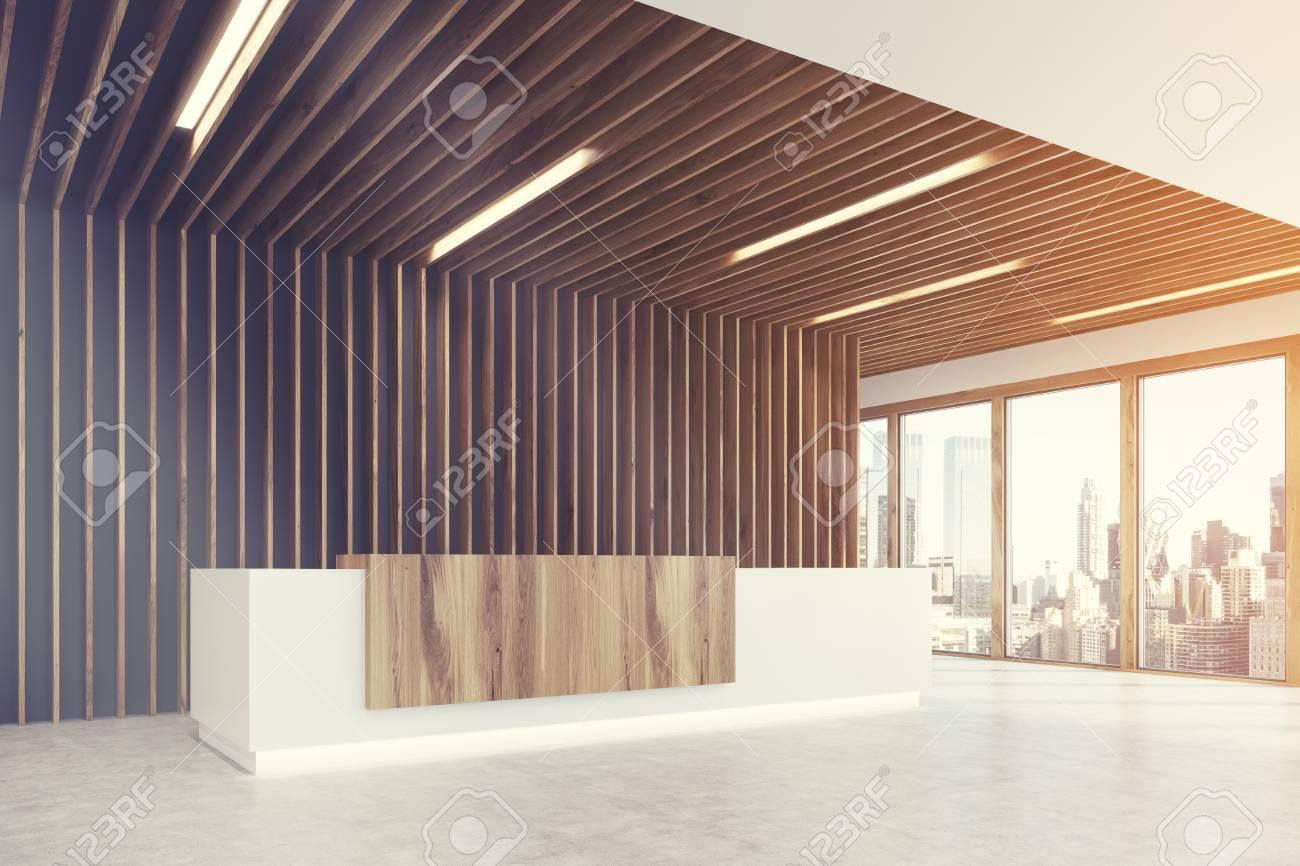 Ufficio Bianco E Legno : Vista laterale di un bancone reception in legno chiaro e bianco è