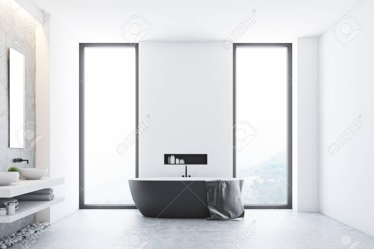 Intérieur de salle de bains moderne blanc avec une baignoire grise se  tenant près d\'une fenêtre, une grande serviette suspendue sur le côté et  une ...