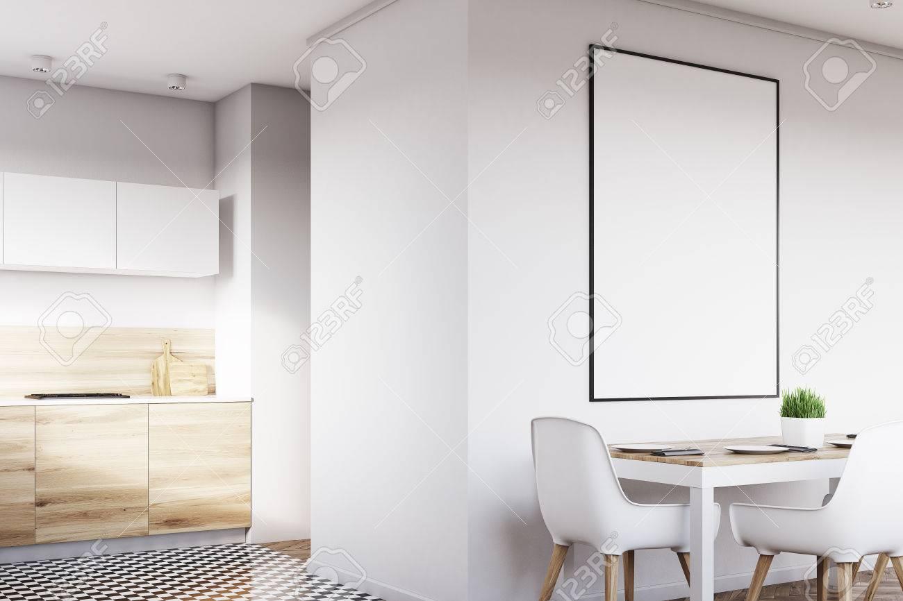 Coin Dun Intérieur De Cuisine Blanc Avec Une Affiche Suspendue Au Dessus Dune Table Avec Des Chaises Les Planchers En Bois Clair Sont Vus En