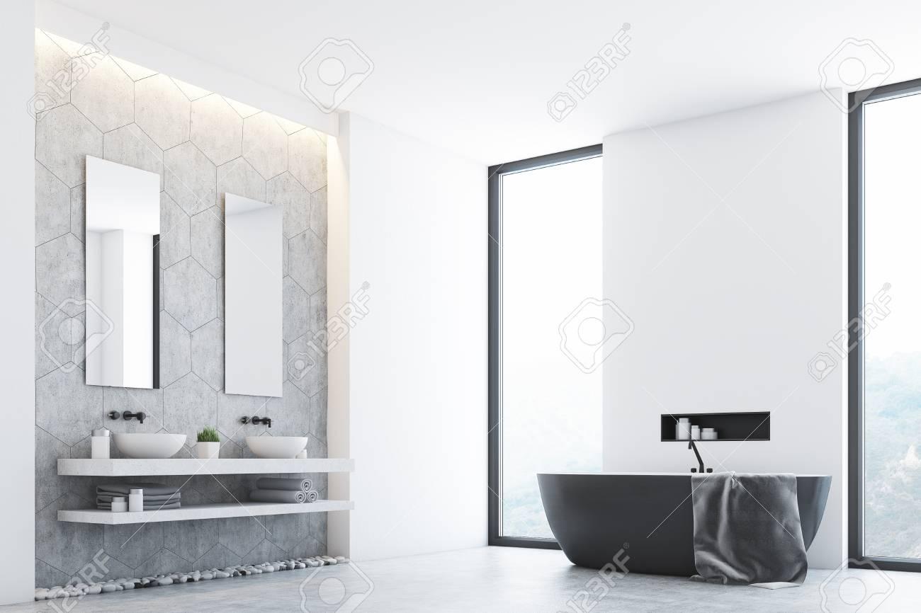 Intérieur de salle de bain moderne gris avec une baignoire grise debout  près d\'une fenêtre, une grande serviette suspendue sur le côté et deux  lavabos ...