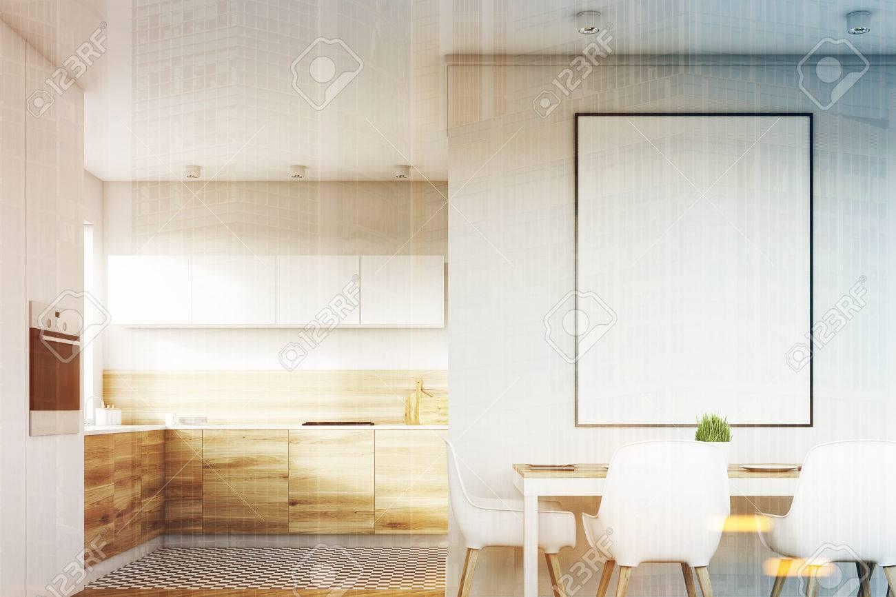 Cuisine Blanche Et Bois Clair vue de face d'un intérieur de cuisine blanche avec une affiche suspendue  au-dessus d'une table avec quatre chaises. les planchers en bois clair sont