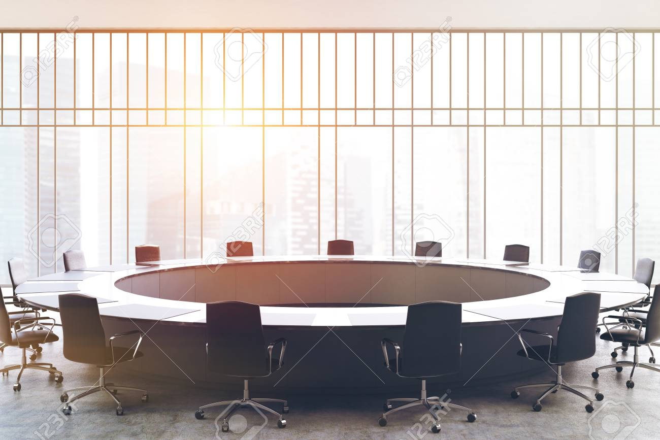 Meeting Room Interior With A Large Black Round Table, Office Chairs  Standing Around It And