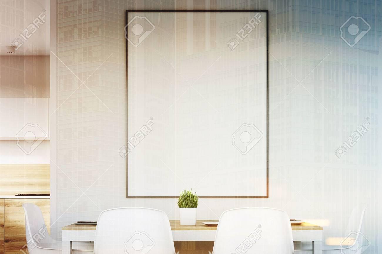 Gros Plan Dun Intérieur De Cuisine Blanc Avec Une Affiche Suspendue Au Dessus Dune Table Avec Quatre Chaises Les Planchers En Bois Clair Sont Vus