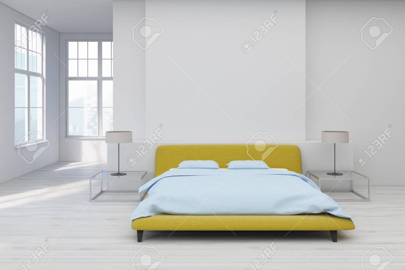 Lit Au Milieu D Une Chambre vue de face de l'intérieur d'une chambre avec un lit double jaune au milieu  d'une pièce avec un sol blanc. table de chevet en verre avec une lampe. la